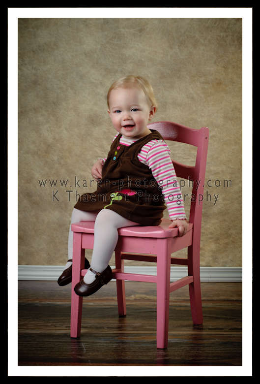 Photo of 1 year old girl on pink chair