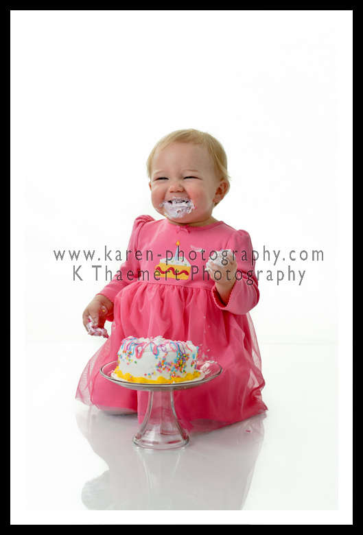 Photo of a 1 year old girl with her birthday cake