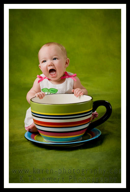 Photo of baby girl at 6 months, next to a giant tea cup.